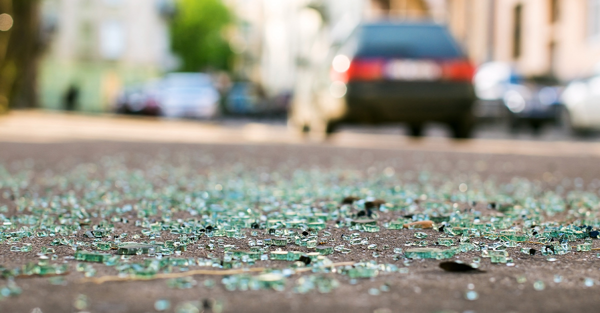 Close-up of shattered glass on pavement with cars in the background