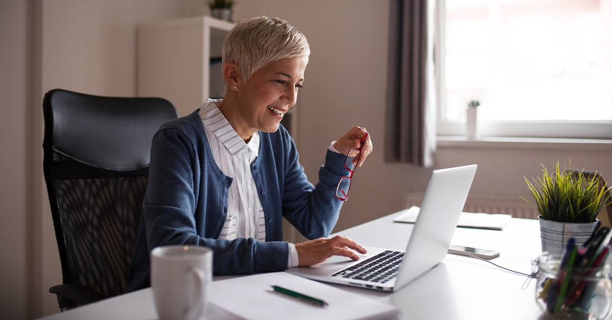 An executive woman working from her home office, sitting in front of a laptop, eyeglasses in hand.